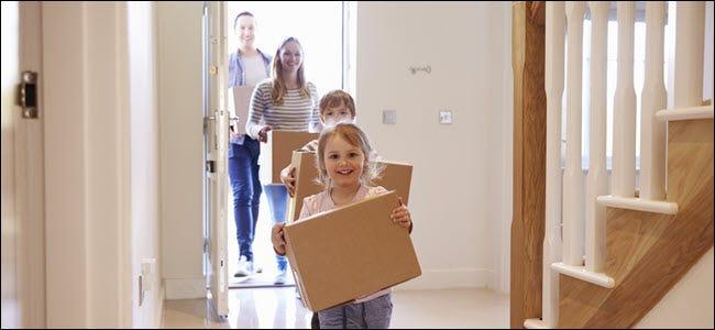 Eine glückliche Familie, die Kisten in einem Haus trägt.