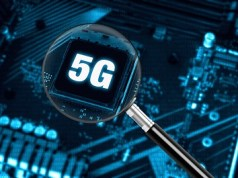 The concept of 5G network with magnifying glass on modern circuit board, high-speed mobile internet and new generation networks technology background