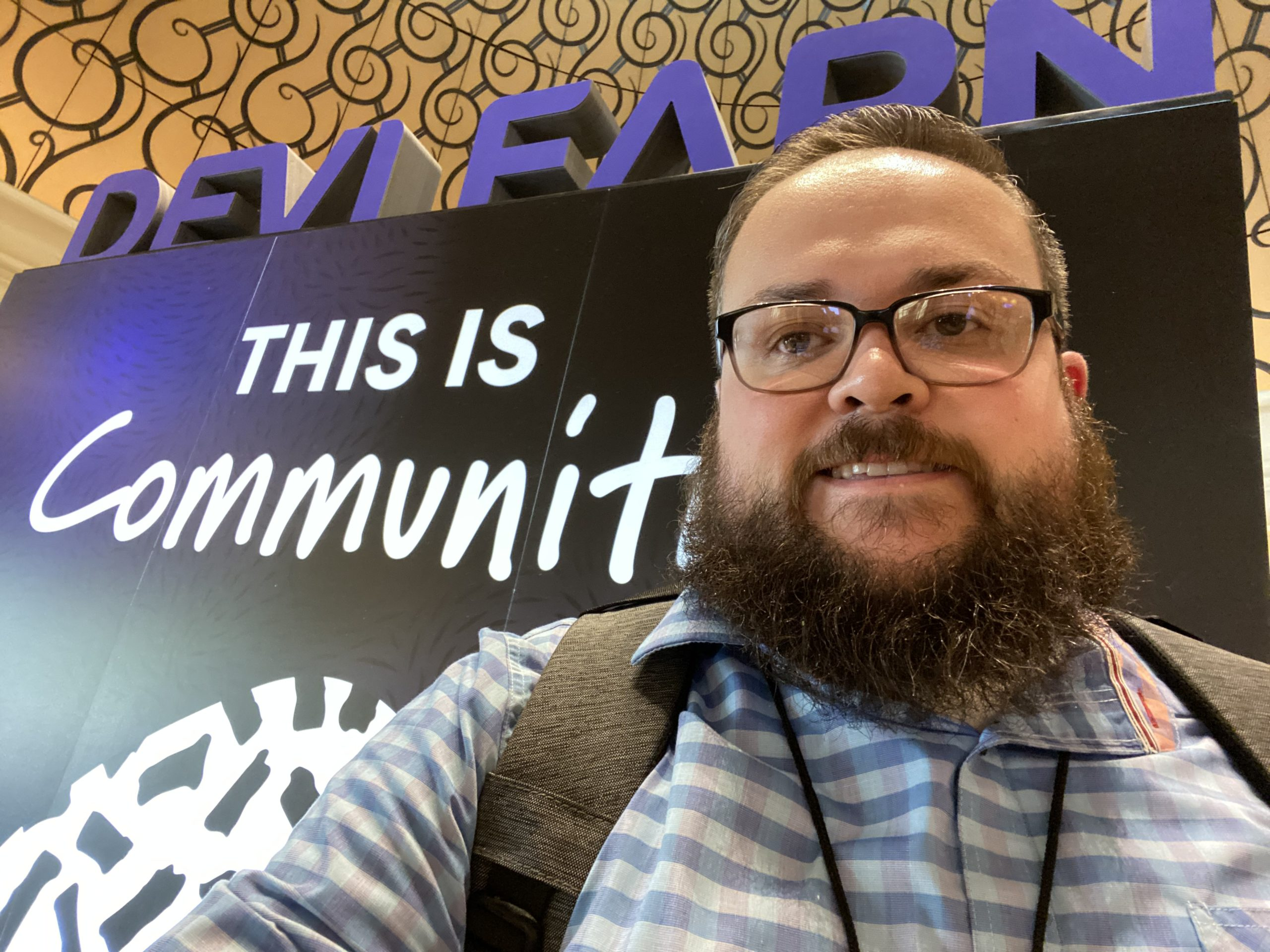 me standing in front of the devlearn this is community sign