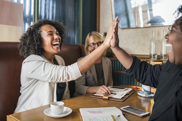 Women high fiving while sitting at a table with cups on it