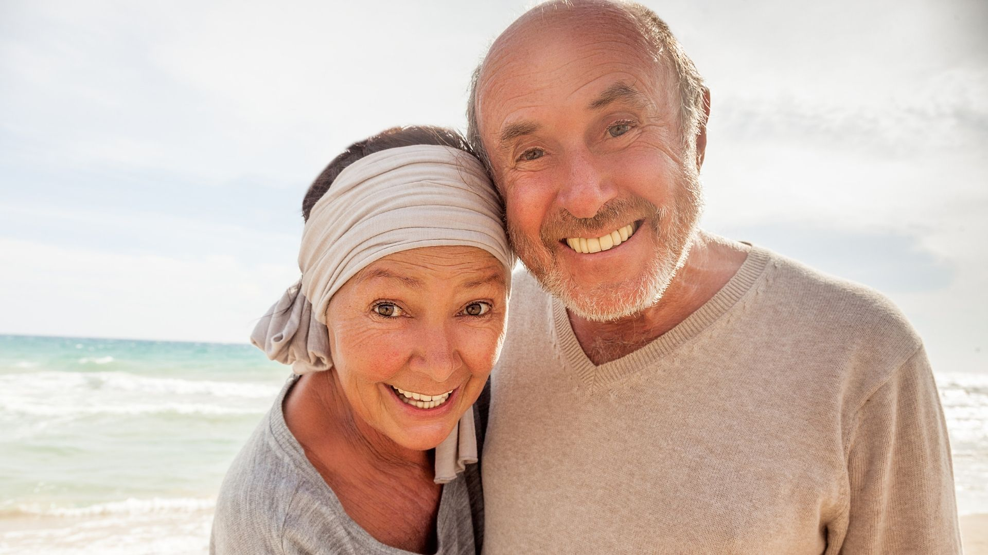 older couple on a beach taking a selfie