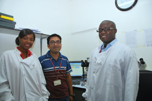 System designer Safayet Hossin (centre) with Malaria laboratory staff Mariama Jallow (left) and supervisor Mortala Ndow (right).
