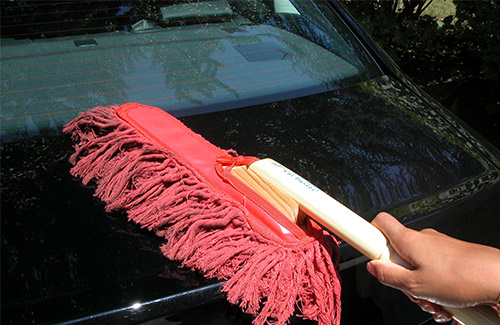 Dusting the car before waterless car wash