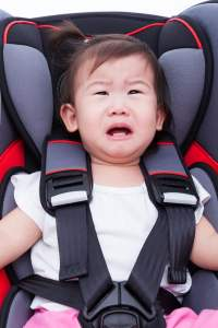Girl crying at car-seat and fasten seat belt