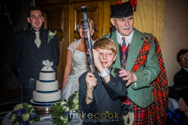 bride and groom, piper, cutting cake, boy, sword, mike cook photography