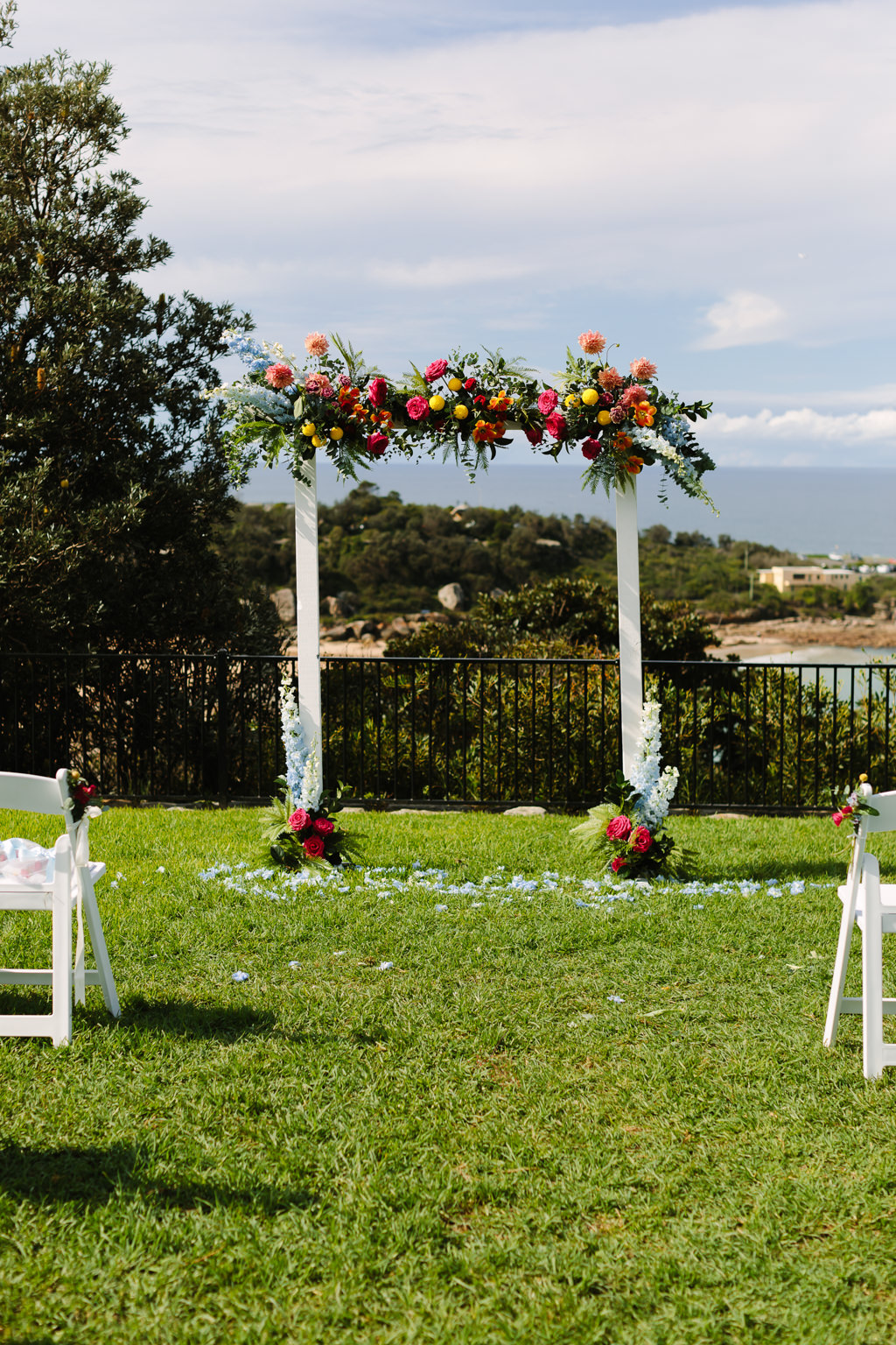 white wedding arbour with colourful flowers - Tropical theme wedding - Gemma Clarke Photography