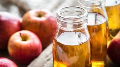 Glass bottles of apple cider vinegar stood next to fresh red apples.