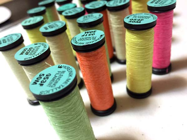 "Kreinik Blending Filament is a thin thread you add to cotton floss or knitting yarn for a lightweight look. The glowing colors carry an ""F"" after the color number, as in 053F."