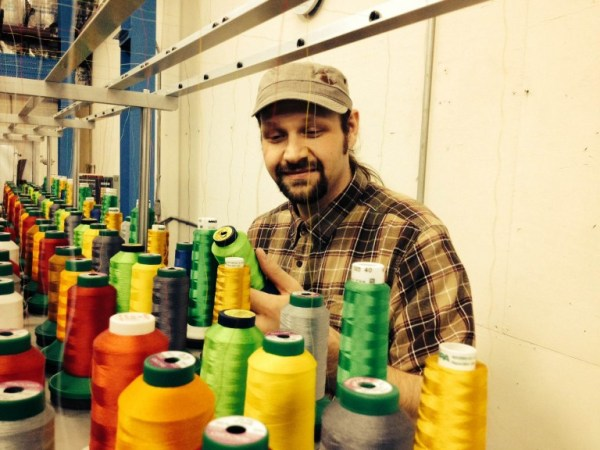 Erich behind a commercial embroidery machine.