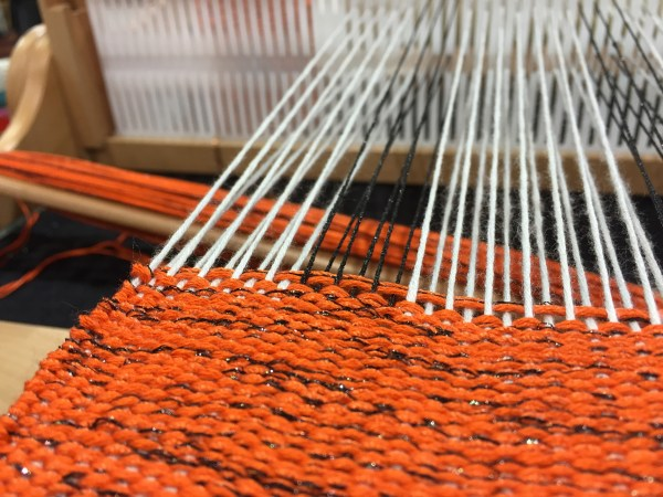"This is one of Doug Kreinik's weaving projects, worked using silk and metallic threads. He used Kreinik Braid in black for warp, and an orange/black combination for the weft. Love the way the metallic adds the ""spice"" of light to the design."
