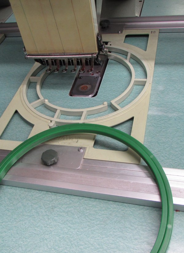 Flat table embroidery machine with round hoop
