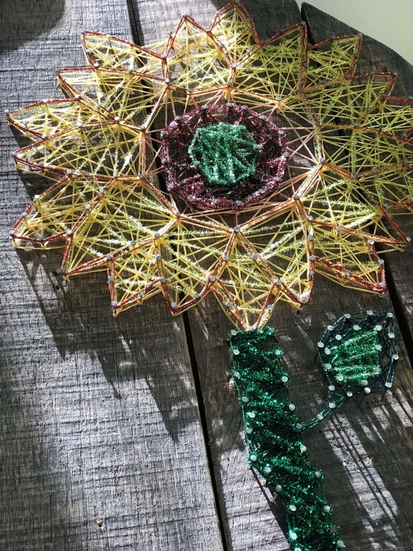 This sparkler was made by Samantha Tornes using a variety of Kreinik threads. She went wild, had fun, and found creative freedom. It's string art.