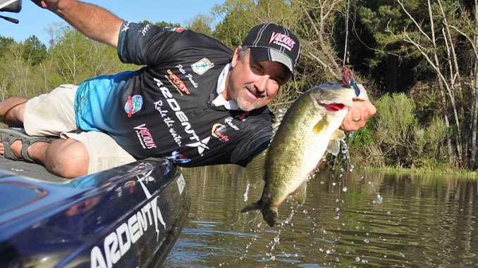 Pete Ponds lands a big male bass in a shallow spawning area on one of his favorite pre-spawn weapons, a swimming jig.