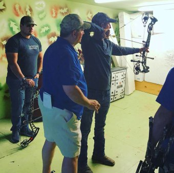 Rod Jenkins gives a shooter tips at an indoor archery range as part of a clinic, one of many the 14-time national champion puts on annually.