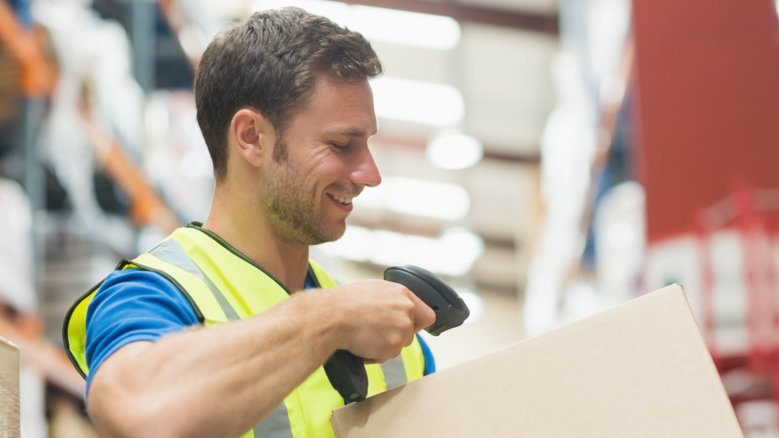 Smiling manual worker scanning package