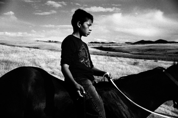 A young boy rides bareback on a horse in the prairie outside the Rocky Boy Powwow in Rocky Boy Agency, Montana.