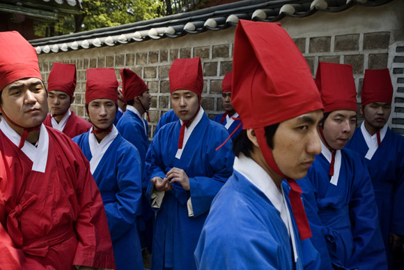 Young men wait for a ceremony to begin during the Jongmyodaeje Festival outside the Jeongjeon Temple at the Jongmyo Shrine in Seoul, South Korea.