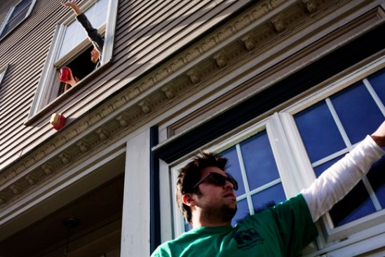 People watch the St. Patrick's Day Parade from windows in houses along the route in South Boston, Massachusetts.