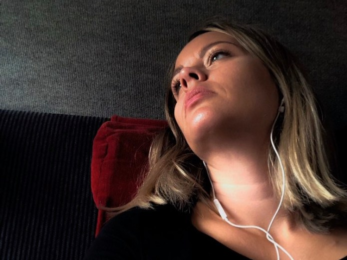 image of a white woman with blonde hair who has her head reclined back and earphones on