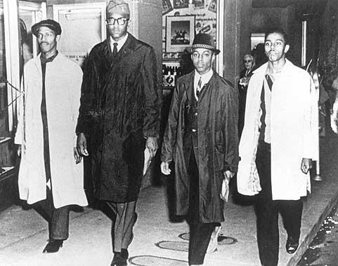 Ezell Blair (sağdan ikinci, kısa boylu ve şapkalı) diğer arkadaşlarıyla oturma eylemini başlattığı gün Greensboro restoranından çıkarken (1 Şubat 1960)