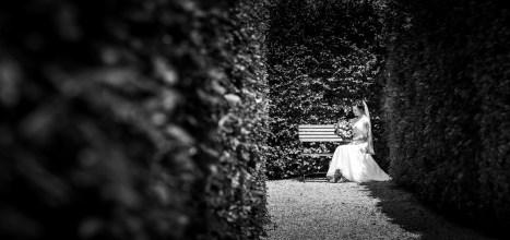bride in gardes sitting on a bench