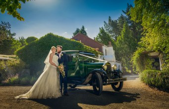 Couple posing by a vintage car, Trents vineyard