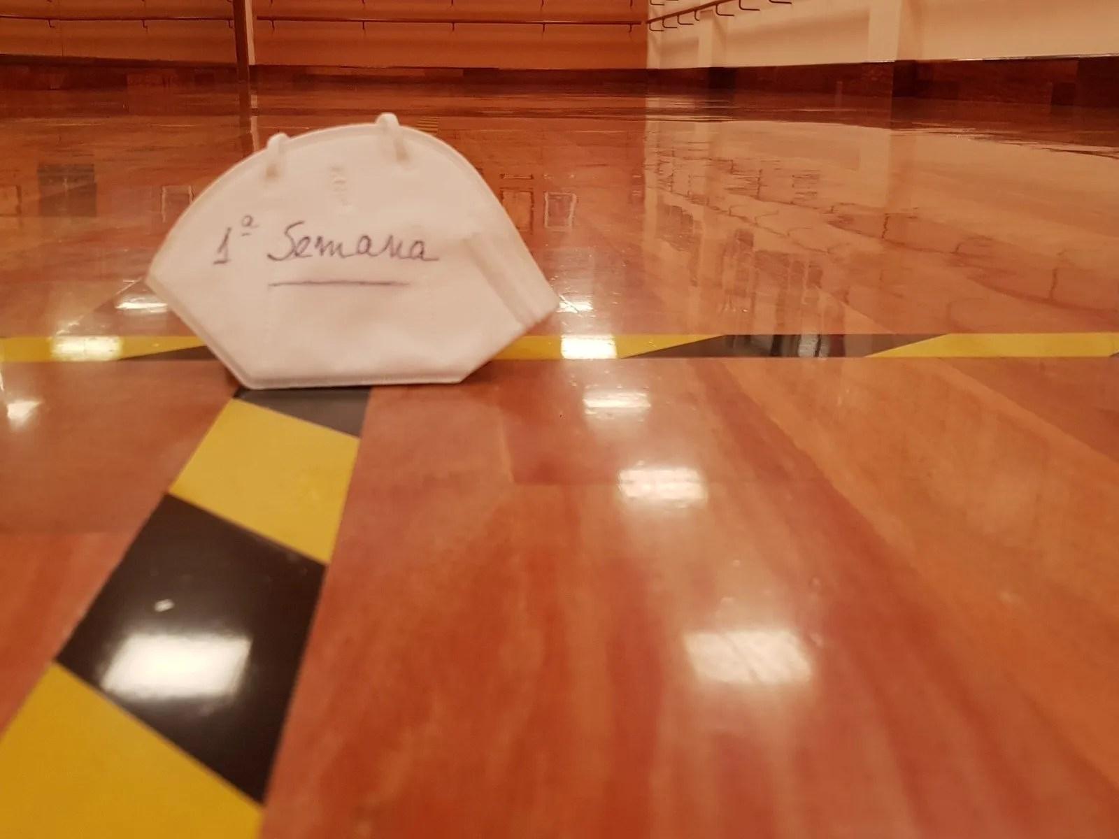 """Foto de una mascarilla que dice """"1ª semana"""". Está sobre las líneas de separación del suelo de la sala de baile del Centro de Danza Sandra Santa Cruz."""