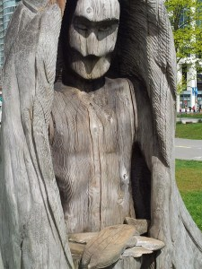 A meditating figure with a bowed head, carved in a tree trunk
