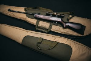 two rifles with fabric brown bags