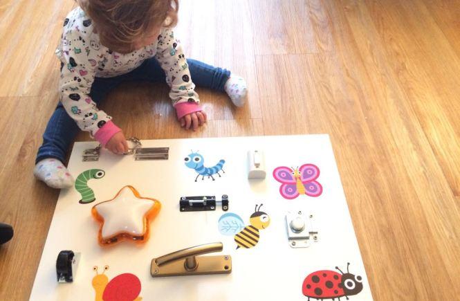 Niña con Sensory Board estilo Maria Montessori para jugar y aprender