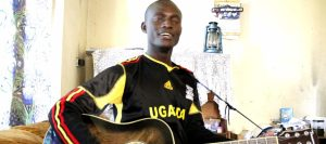 Mukalele Rogers trying out a guitar at home in Jinja Town