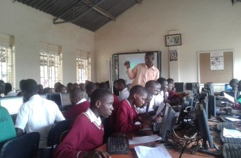 Teacher Guiding Students using computers in a computer Lab