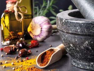 herbs and spices being prepared with pestle and mortar