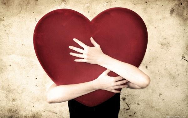 Mulher abraçando coração gigante