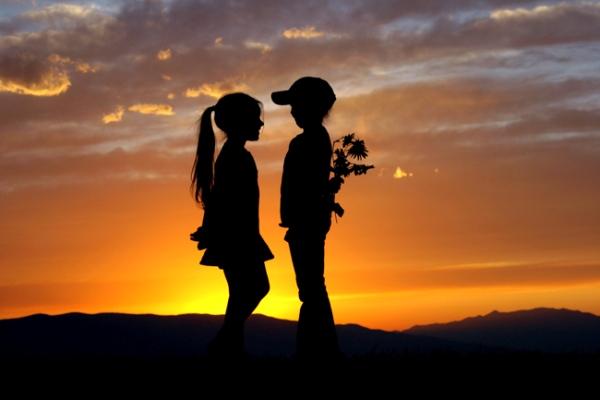 Menino e menina se amando ao pôr-do-sol
