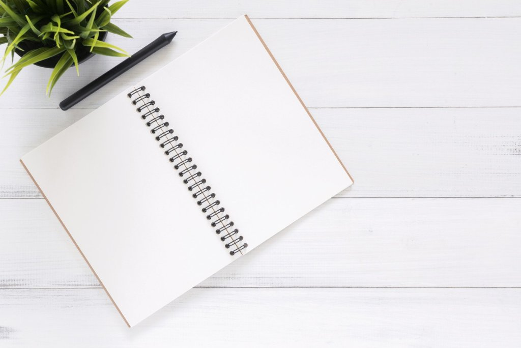 white desk with plant and clean pages of a notebook for writing a job description