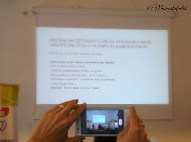 mano che fotografa con cellulare la schermata del momclass mammacheblog 2015 dell' 8-9 maggio organizzato da fattoremamma