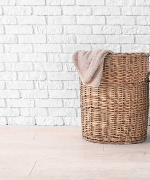 A straw laundry basket sits with its lid leaning against it and a towel hanging over the edge