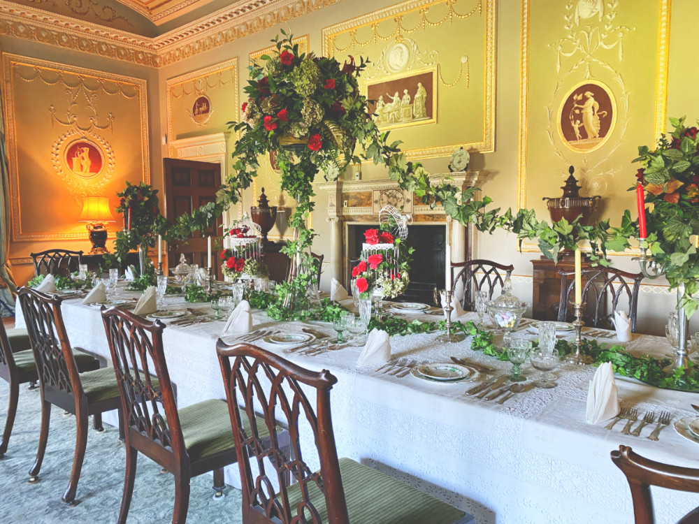A table at Basildon Park National Trust house laid for dinner. There is a white table cloth, lots of greenery and place settings for 20