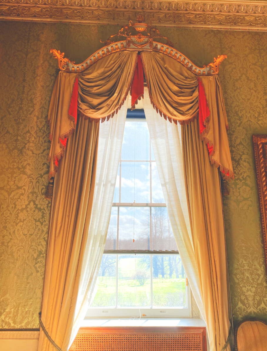 A window at Basildon Park looks out over the lawn. The window is framed by draped curtains in a mustard and red colour