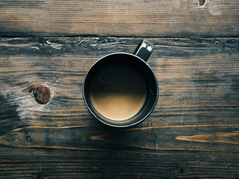 Looking down on a mug of coffee on a wooden counter