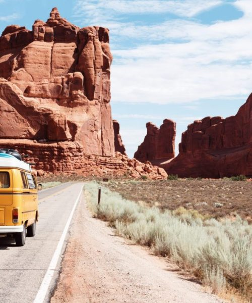 A yellow VW camper van drives along a deserted road towards red coloured mountains