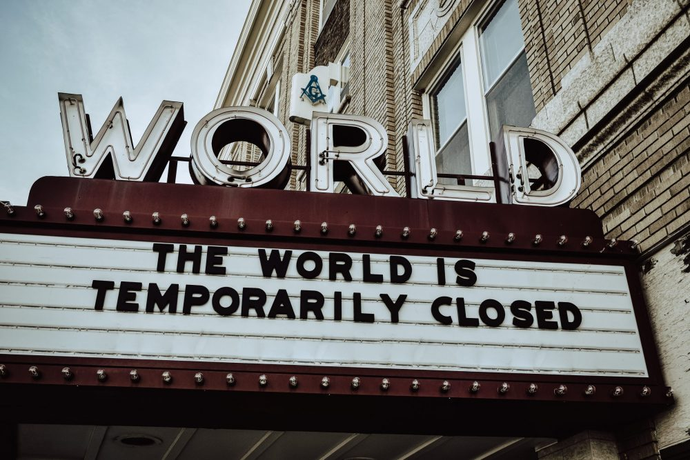 """A sign below the World Cinema saying """"The world is temporarily closed"""""""