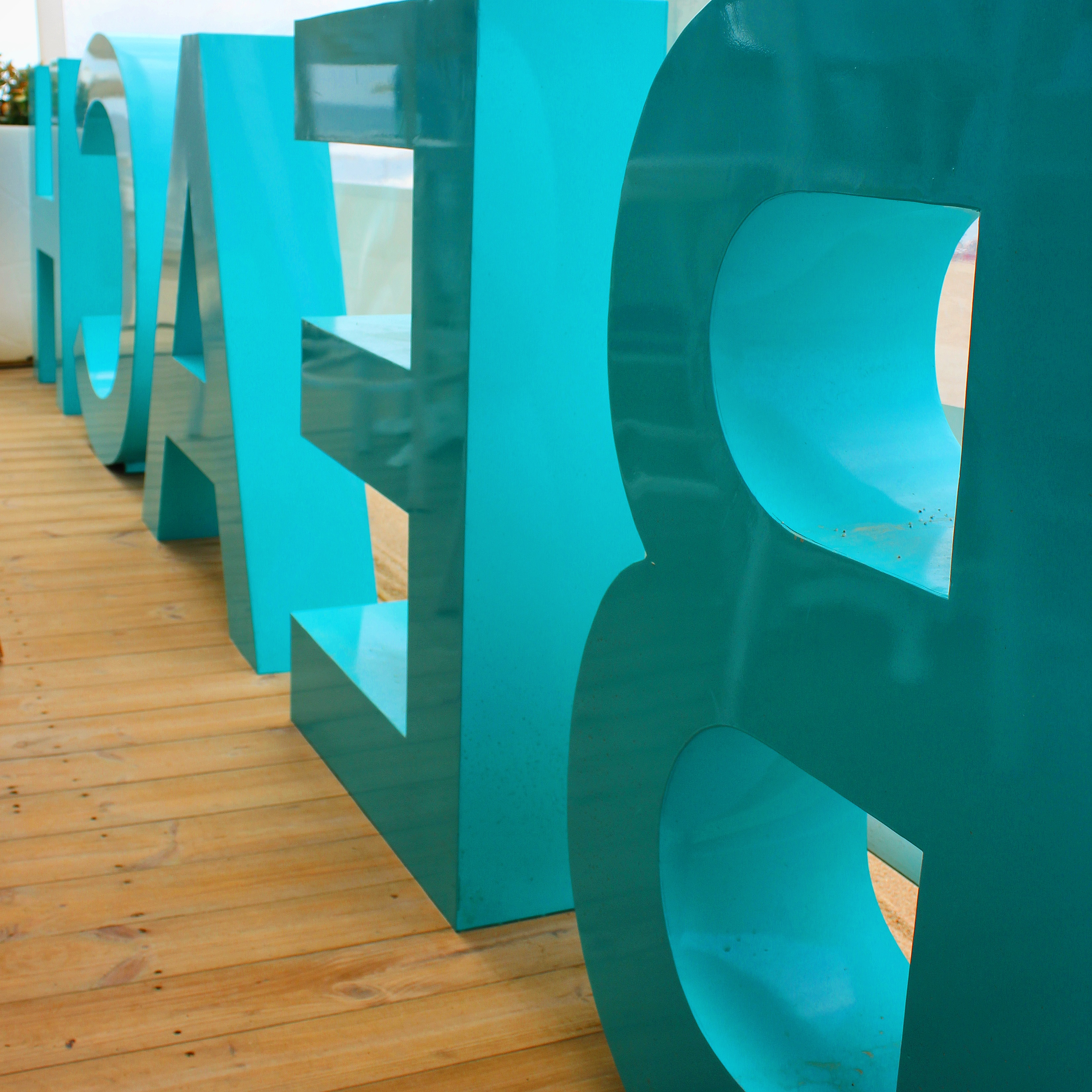 Reverse view of the big turquoise letters spelling beach at Nui Beach Club near Calella. My photo tour of Costa Barcelona