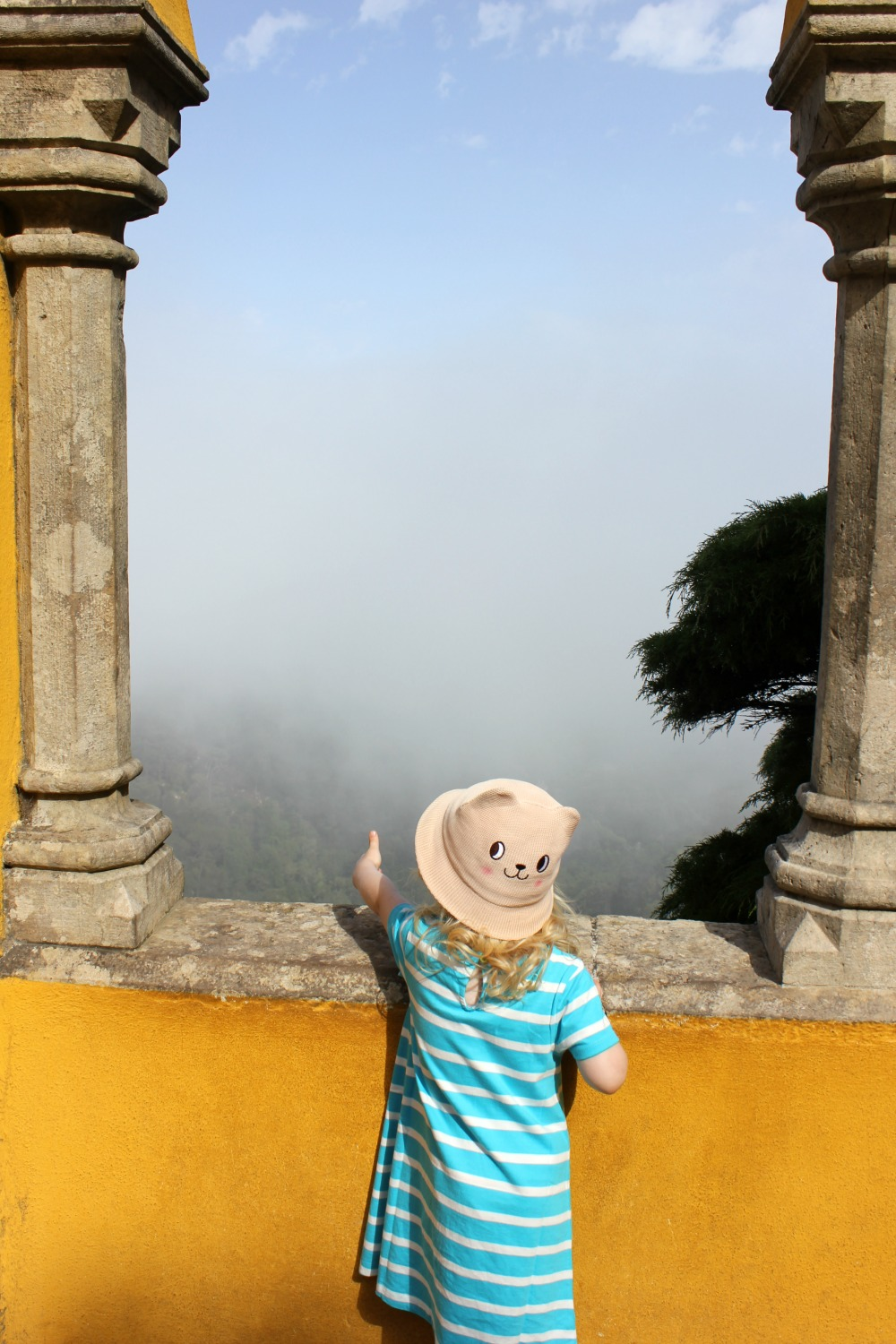 A girl looks out between the pillars and yellow painted walls of the Pena Palace at Sintra onto a misty view - one of my favourite memories of the country and among Portugal's most unusual attractions