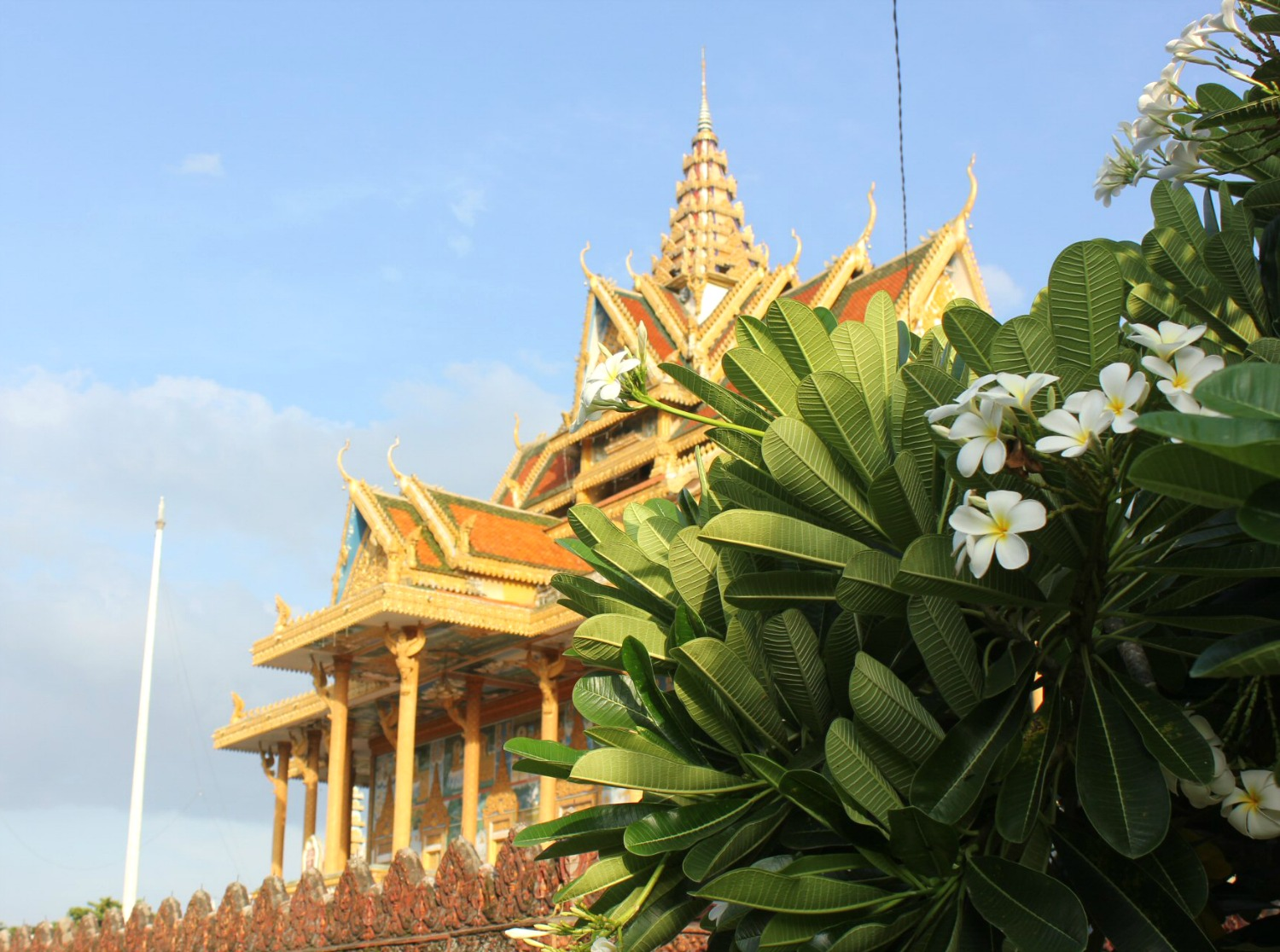 A golden and orange temple agains a blue sky at the end of the day in Battambang - 12 reasons to visit Cambodia with kids