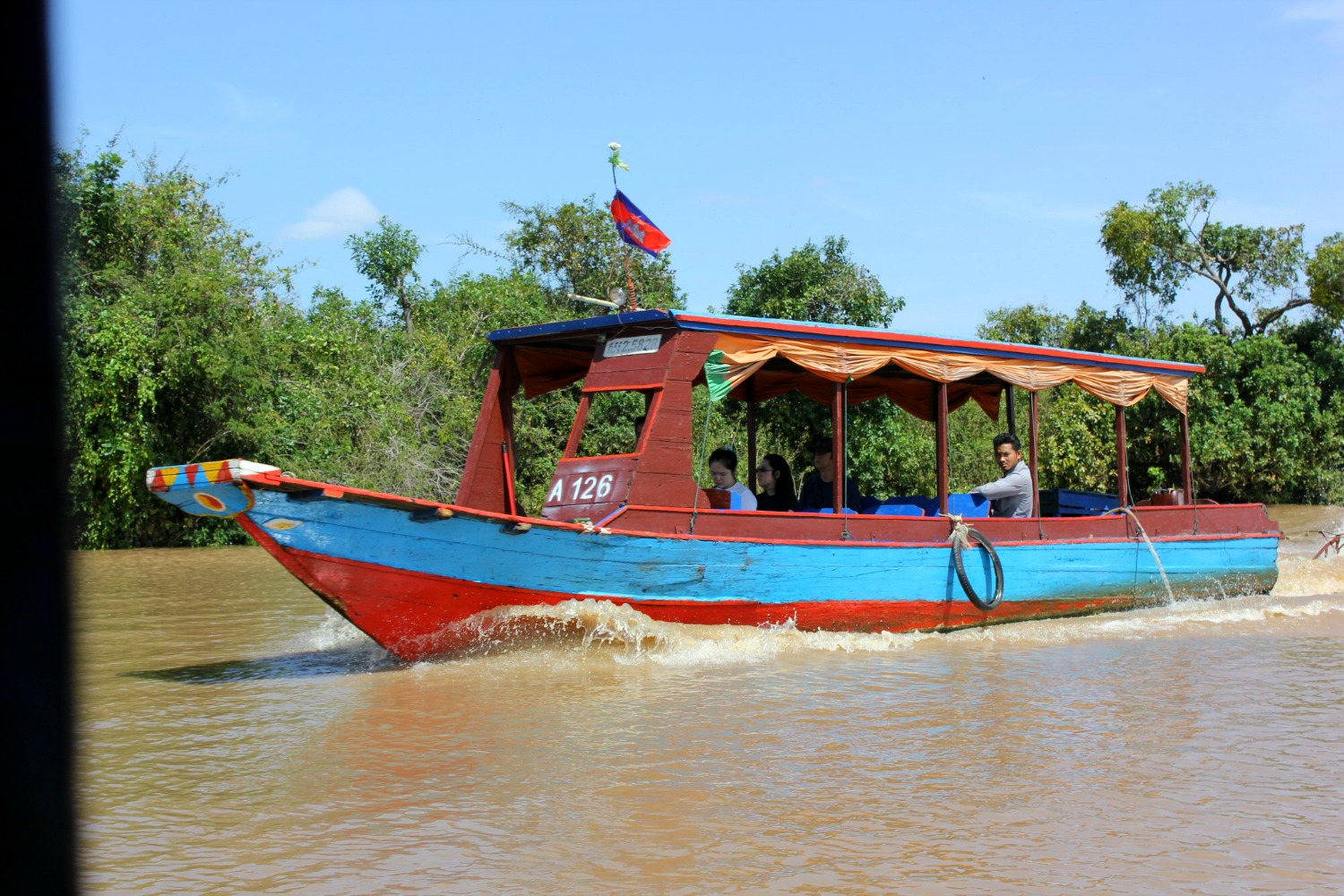 Bright red and blue boat on the river near Tonle Sap - 12 reasons to visit Cambodia with kids