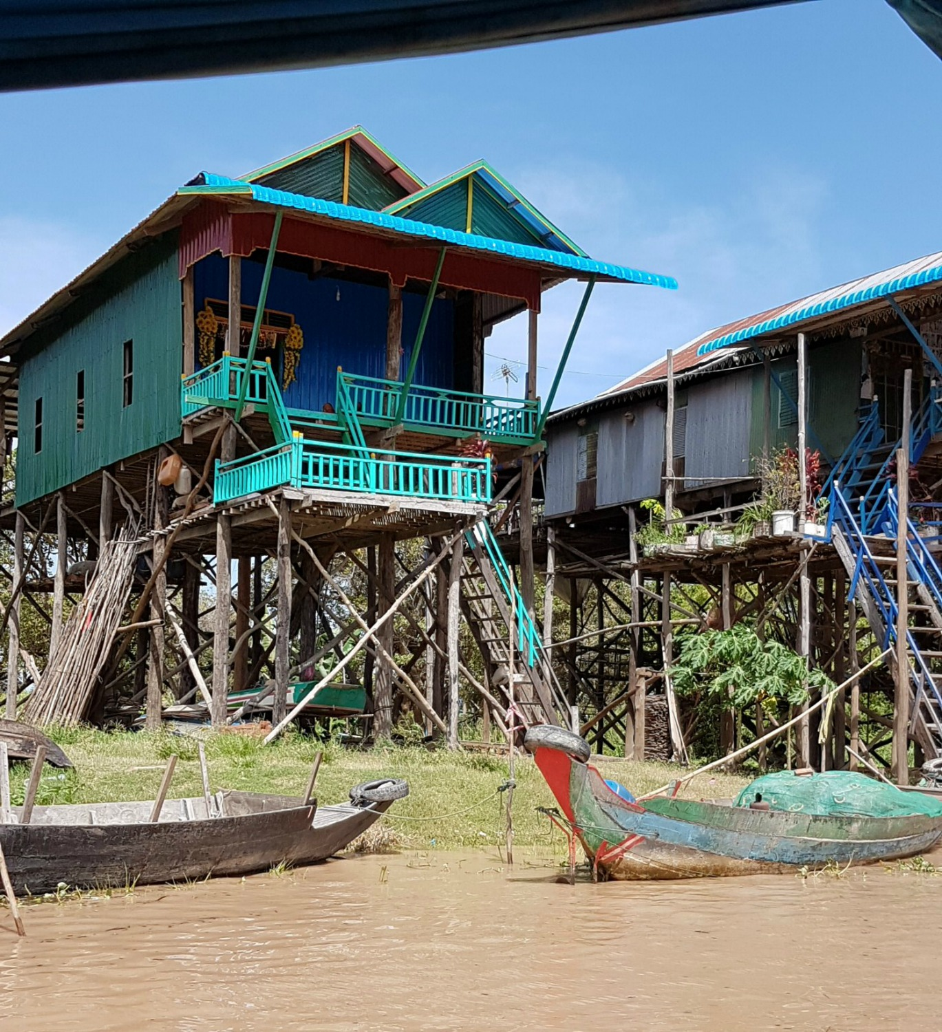 Bright turquoise stilt house by Tonle Sap - 12 reasons to visit Cambodia with kids