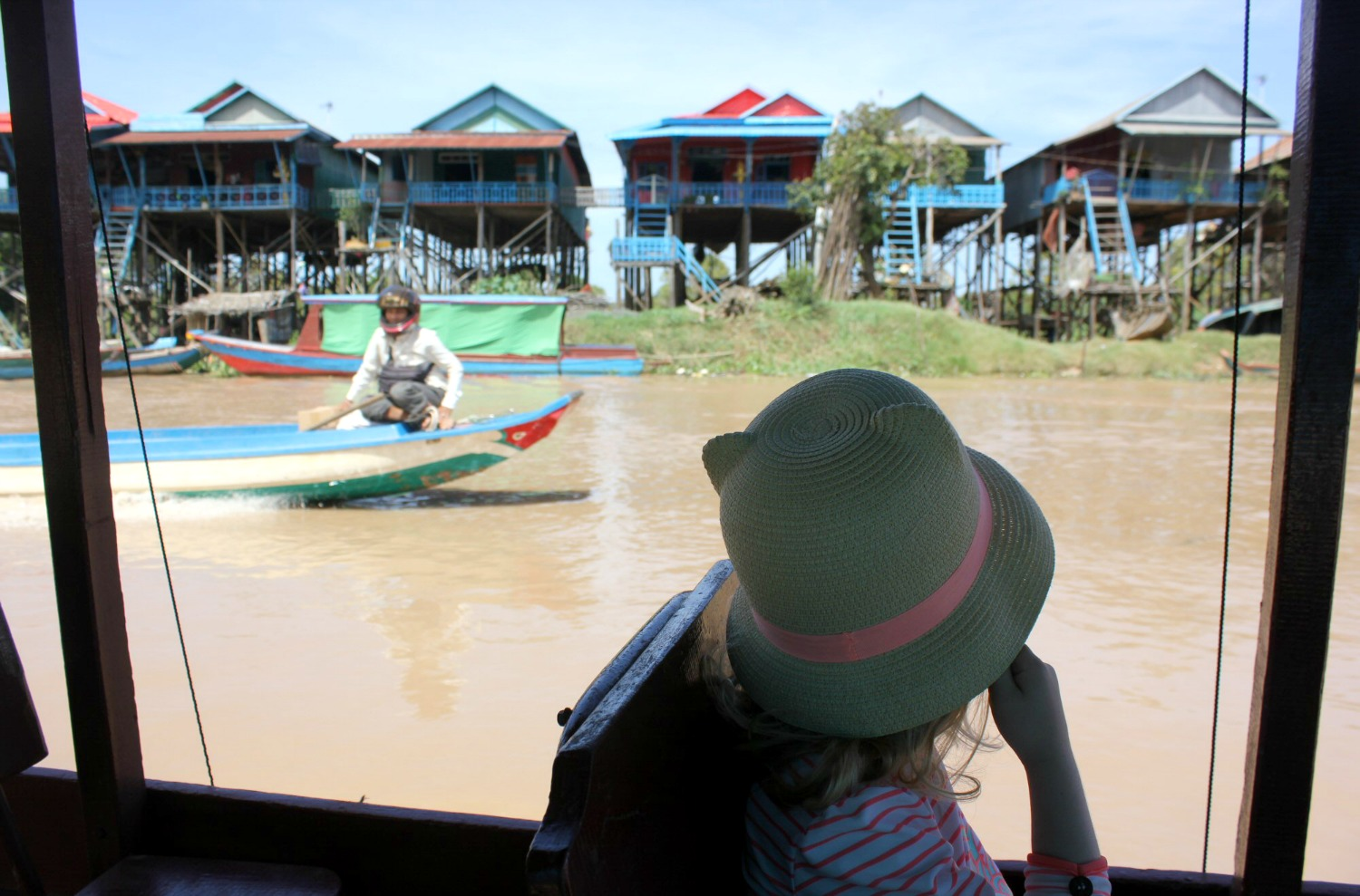 My daughter looks out of a boat onto a line of stilt houses near Tonle Sap lake - 12 reasons to visit Cambodia with kids