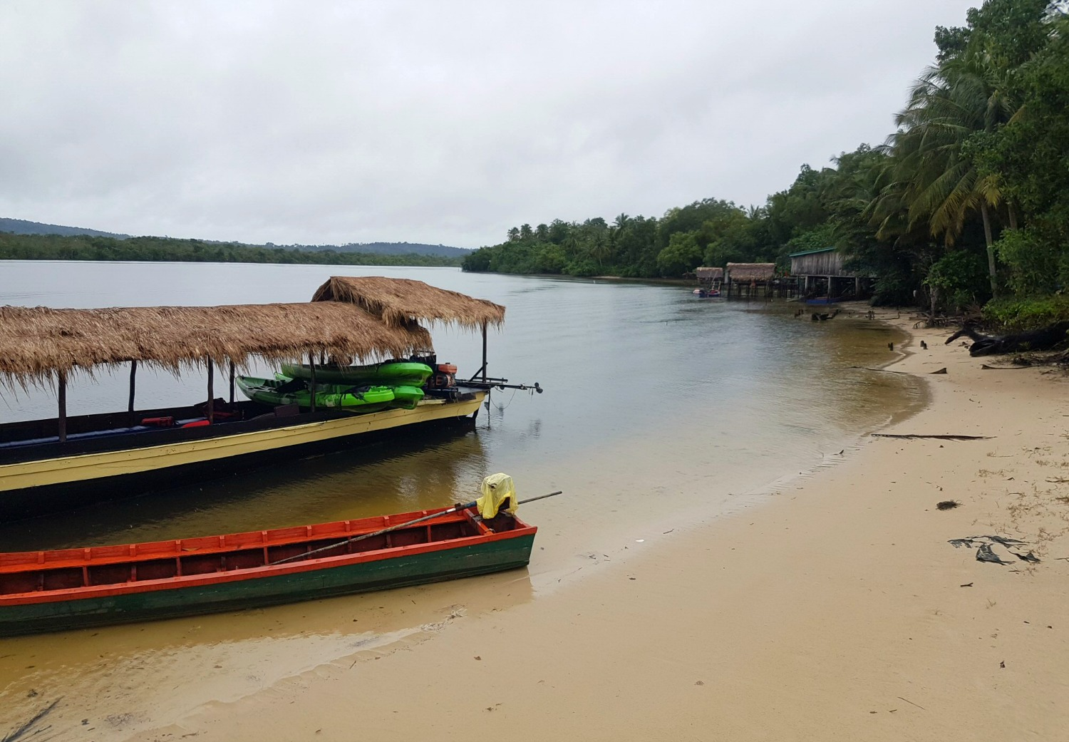 Boat moored at a beach along the river Tatai to explore a local school and village - discovering Cambodia's Cardamom Mountains with kids